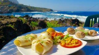 Déjeuner en front de mer à Garachico. Au menu calamar à la plancha fraìchement pêché avec en arrière plan les fameuses papas agurradas accompagnées de son mojo verde