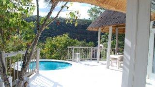 La terrasse et la piscine des chalets au Clifftop Exclusive Lodge