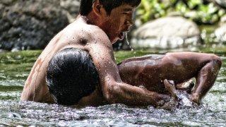 Les enfants de la communauté se baignent et jouent dans la rivière